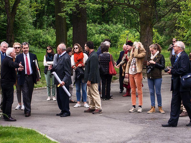 Grupa ludzi stojących na ścieżce w parku przed pałacem, w tle dzrewa.
