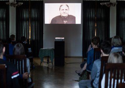 Wykład na ekranie wyświetlone zdjęcie starszej kobiety.