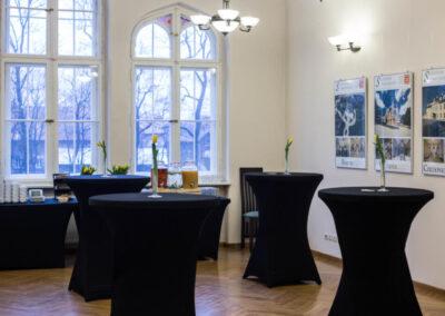 Okrągłe stoliki okryte czarnym suknem.
