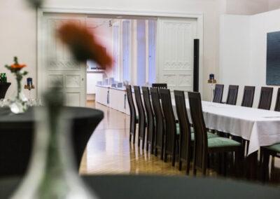 Długi stół przykryty białym obrusem. Przy stole krzesła.
