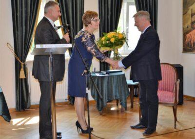 Mężczyzna i kobieta wręczajacy kwiaty profesorowi Miodkowi.