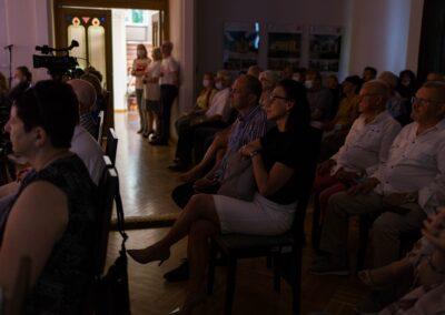 Ludzie siedzący w rzędach i słuchajacy koncertu.
