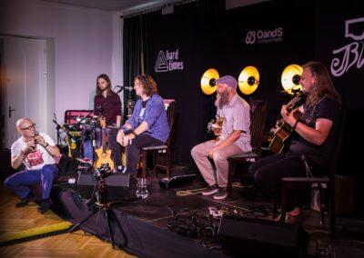 Czterech mężczyz grających na instrumentach, mężczyzna siedzi na secenie i mówi do mikrofonu.