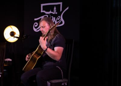 Mężczyzna z długimi włosami grający na gitarze.