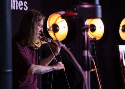 Mężczyzna z długimi włosami grający na skrzypcach, w tle dwa reflektory.