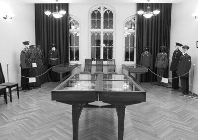 Sala wystawowa, na środku stół, wystawa mundurów.