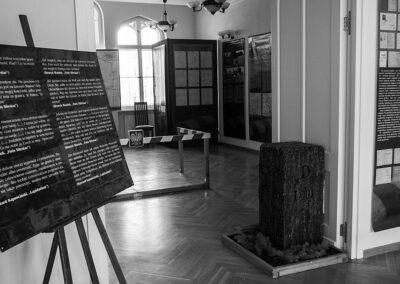 Sala wystawowa, z lewej plansza, w tle inne pomieszczenie.