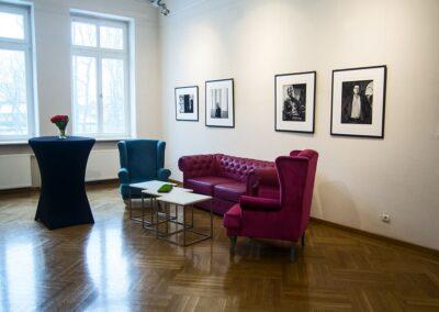 Duża sala, po prawej różowa sofa i turkusowy fotel. Po lewej okrągły stolik pokryty czarnym suknem.