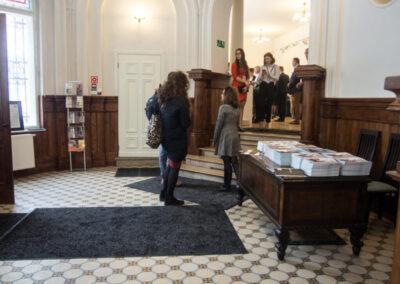 Wejście, duzy drewniany stół z książkami. Zwiedzający.