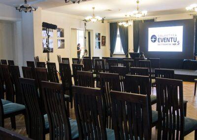 Pusta sala wykładowa. Krzesła, w tle ekran.