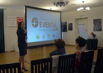 Wykład, kobieta z mikrofonem, w tle prezentacja na ekranie.