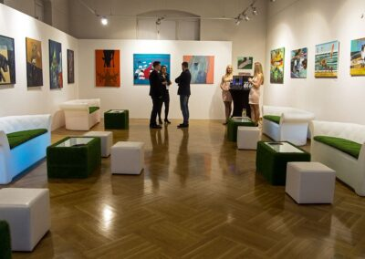 Duża sala wystawowa. Na scianach obrazy. Dookoła rozstawione pufy i fotele.