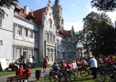 Grupa rowerzystów przed pałacem.