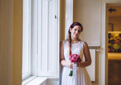 Panna młoda z kwiatami, oparta o ściane porzy oknie.
