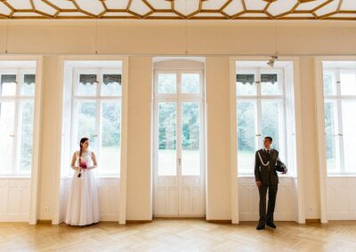 Państwo młodzi w dużej sali na tle okien.