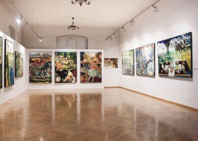 Sala wystawowa, lśniący parkiet, kolorowe, abstrakcyjne obrazy na ścianach.