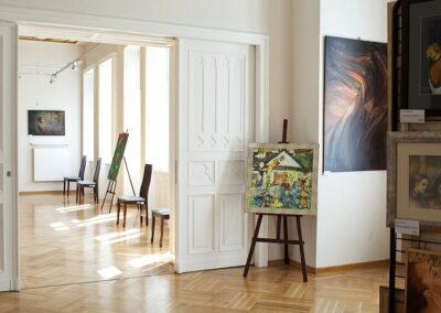 Sala wystawowa, ekspozycja obrazów, drzwi prowadzące do kolejnej sali.