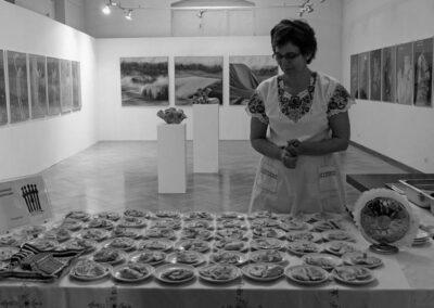 Na scianach obrazy. Kobieta stoi przy stole z talerzami z jedzeniem.