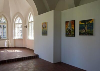 Sala wystawowa, biała sciana, obrazy, w tle gotyckie okna.