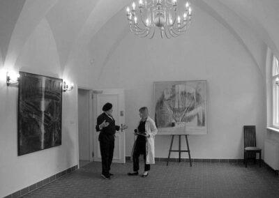 Czarno-białe zdjęcie sali wystawowej. Na scianach obrazy. Po srodku dwóch mężczyzn.