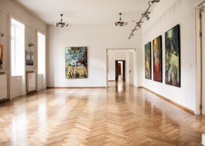 Sala wystawowa z kolumnami, na których wiszą obrazy.