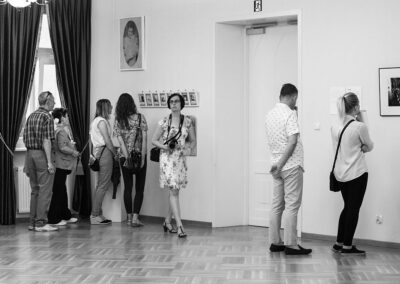 Czarno-białe zdjęcie sali wystawowej ze zwiedzajacymi.
