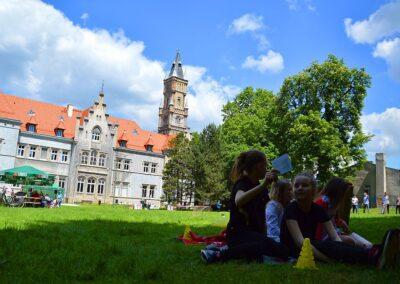Dzieci rysujące na kartkach, w tle pałac w Nakle Śląskim.