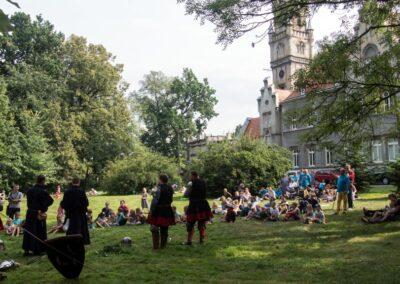 Ludzie bawiący się na trawniku przed pałacem.