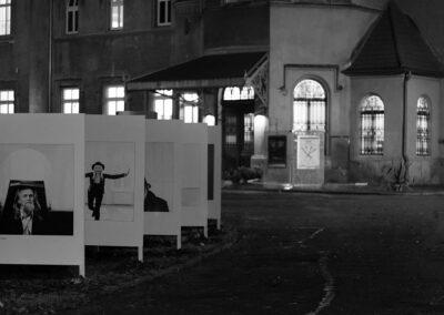 Czarno-biale zdjęcia znanych osób na planszach ustawione w parku.