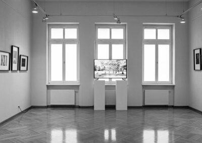 Czarno-białe zdjęcie sali wystawowej. Na wprost duże okna.