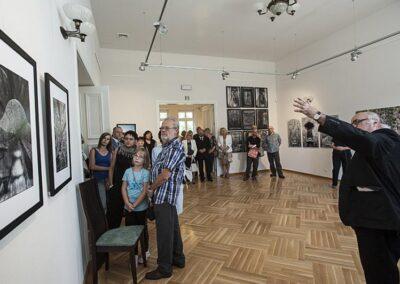 Sala wystawowa, po prawej mężczyzna tłumaczący coś zebranym osobom.