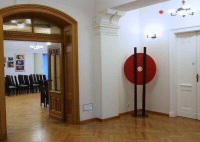 Duże drewniane drzwi prowadzące do sali koncertowej. Pop prawej czerwony gong na stojaku.