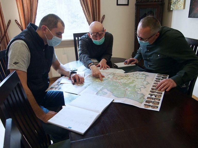 Trzech mężczyzn w maseczkach, siedzących przy stole i patrzących na rozłożone mapy.