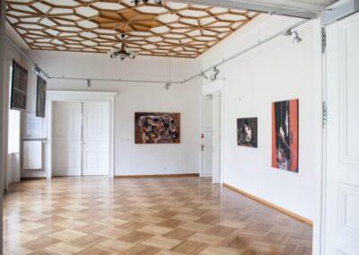 Sala wystawowa ze zdobionym rozetami sufitem. Na scianach obrazy.