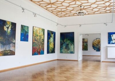 Sala wystawowa ze zdobionym rozetami sufitem. Na scianach kolorowe obrazy.
