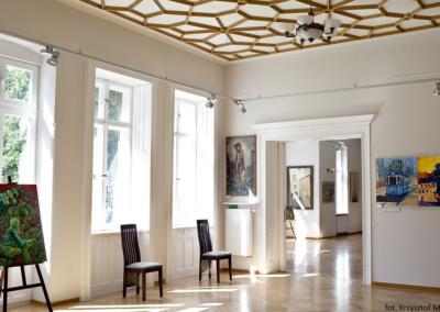 Sala wystawowa ze zdobionym rozetami sufitem. Na scianach obrazy.Pod oknami stoją krzesła.
