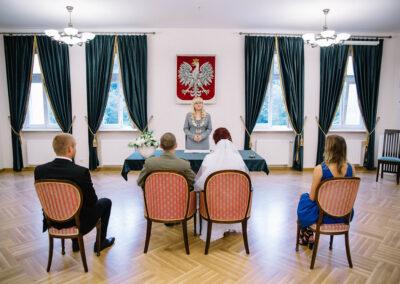 Cztery osoby siedżce tyłem na obitych, czerwona tapicerka krzesłach. Przed nimi stoi urzędzniczka stanu cywilnego. Z tyłu na scianie godło Polski.