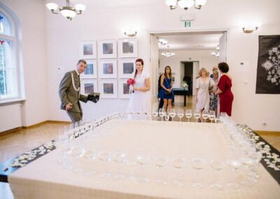 Duzy stół z kieliszkami szampana. Panna młoda i pan młody w mubdurze wojskowym galowym.