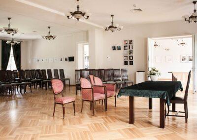 Duża sala. Z przodu stół z zielonym suknem. Za nim antyczne krzesła obite czerwoną tapicerką. W tle rezędy krzeseł.