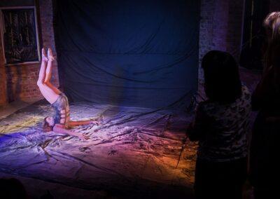Dziewczyna wykonująca akrobację, po prawej osoba robiąca zdjęcie.