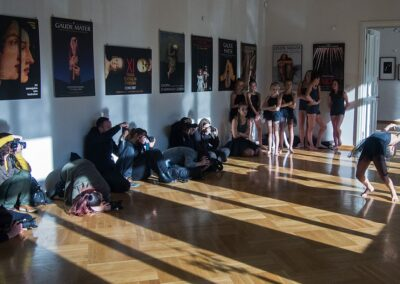 Grupa osób siedząca na podłodze z aparatami fotograficznymi.