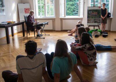 Mężczyzna w przebraniu gra na keyboardzie, na podłodze siędzą dzieci.