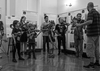 Czarno-białe zdjęcie Mężczyzna i grupa dzieci ze skrzypcami.