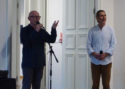 Z lewej mężczyna ubrany na czarno (dyrektor Zając) mówiący do mikrofonu, z prawej mężczyzna ubrany na jasno (Jacek Świgulski)
