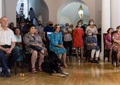 Elegancko ubrani ludzie siedzący na krzesłach lub stojący z tyłu.