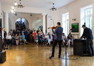 Tył mężczyzny grającego na skrzypcach. Przed nim ludzie stojący isiedzący słuchają muzyki.
