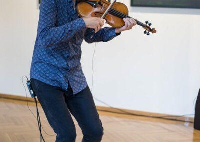 Mężczysna w oklularach z brodą i wąsem grający na skrzypcach.