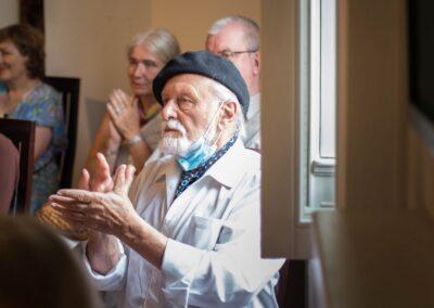 Starszy mężczyzna z siwą brodą i wąsem w czarnym berecie bijący brawo.