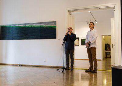 Po prawej dwóch mężczyzn. Jeden w białej koszuli (Jacek Świgulski), drugi ubrany na czarno 9dyrektor Stanisław Zając). Po prawej na ścianie wisi długi obraz. W tle druga sala.