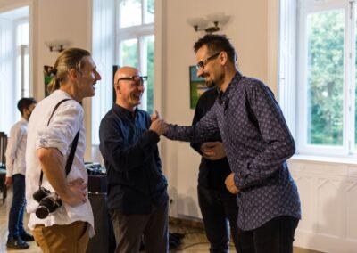 Trzech mężczyzn: z lewej Jacek Świgulski w białej koszuli, po srodkudyrektor Stanisław Zając przybijający piątkę ze stojącym po prawej stronie Marcinem Sidorem. Z tyłu widac sylwetke mężczyzny ubranego na czarno.